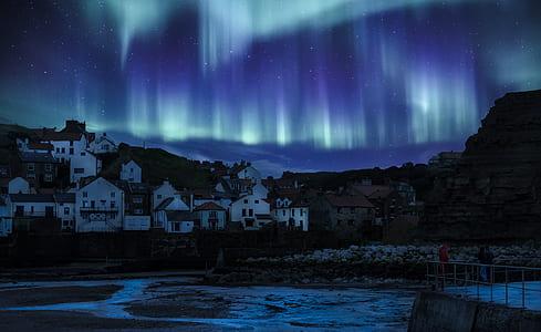 aurora borealis above villlage