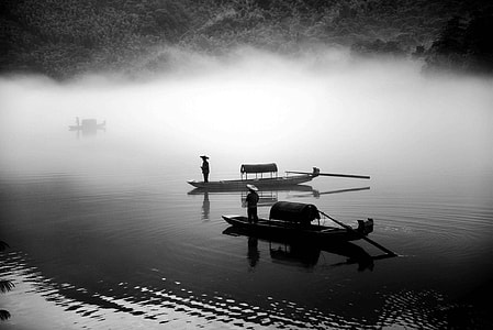 two man in boats on body of water grayscale photography