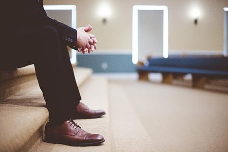 man in black suit sitting on brown stairs