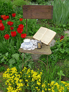 teacup and book on chair surrounded with flowers