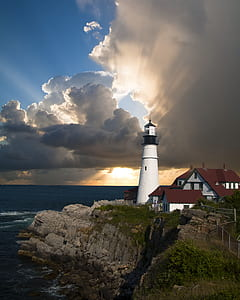 photo of white lighthouse near body of water