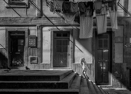 grayscale photo of person walking on stair beside house