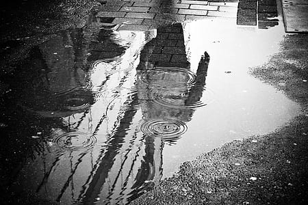 greyscale photography of puddle on grey concrete floor