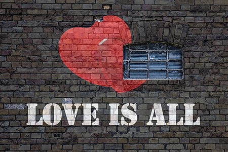 LOVE IS ALL painted brick wall