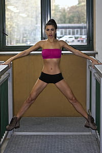 woman exercising wearing pink micro top and black micro shorts