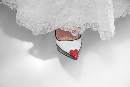 unpaired white leather heeled shoe