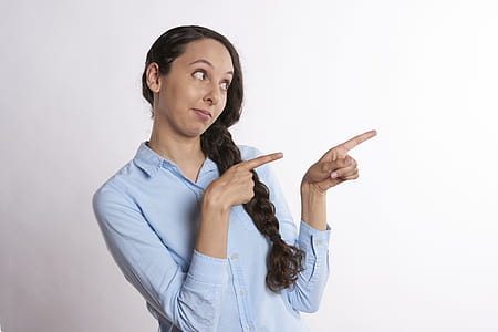 woman pointing her two index fingers on right side