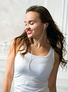 woman wearing white tank top and white earphones standing inside well lighted room