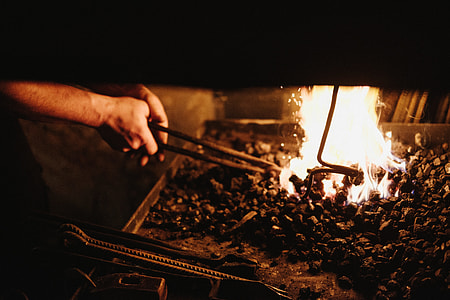 person holding black metal tong near fire