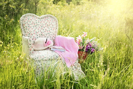 white, green, and pink floral fabric sofa chair with pink textile and hat on grass