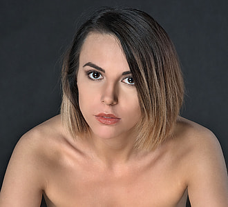 topless woman against black background