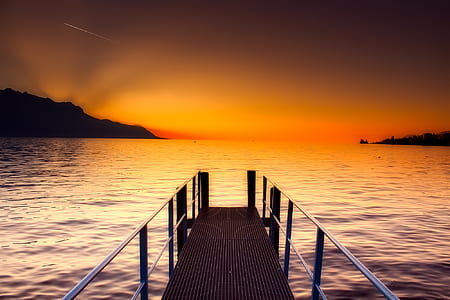 wooden dock on body of water with silhouette of mountains at distance