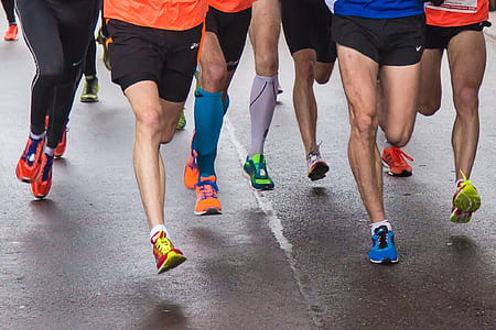 group of people wearing running shoes running on road