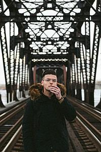 man wearing black fleece coat standing on concrete bridge during daytime