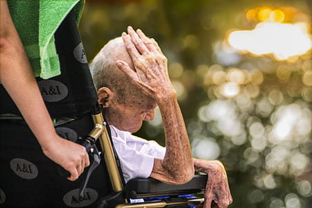selective focus photography of man sitting on wheelchair