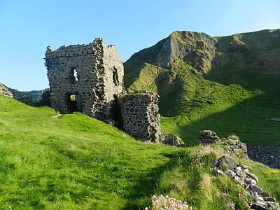 gray concrete ruins on green grasses