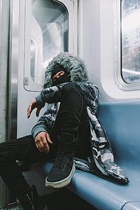 man wearing jacket on train sleeping