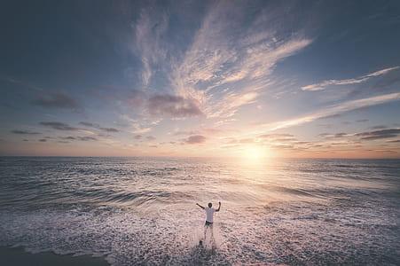 person standing facing seashore