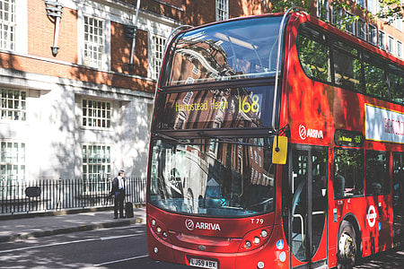 A classic red London bus sits in dappled sunlight on a road in Central London, image captured with a Canon DSLR