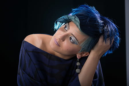 woman with short blue hair wearing blue and black off-shoulder top