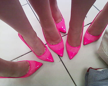 three women wearing pink patent leather pointed-toe heeled shoes