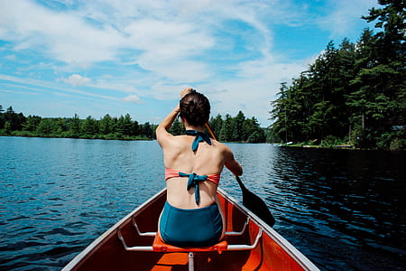 woman wearing teal and red bikini set while using a boat paddle