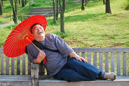 man laughing while sitting on bench holding oil paper umbrella
