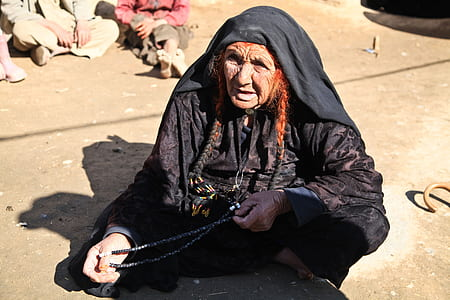woman sitting holding beaded necklace
