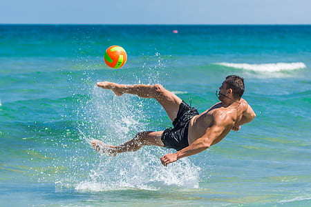 man kicked ball on body of water