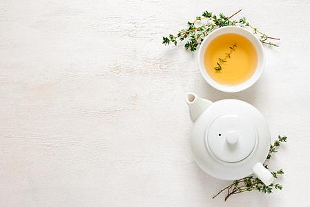 white ceramic teapot beside teacup with tea
