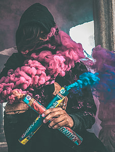 person in black hoodie holding blue and purple rainbow smoke makers