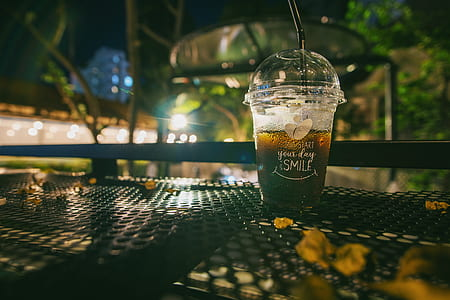 Clear Plastic Disposable Cup With Straw Half-filled With Juice on Metal Table
