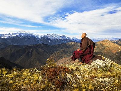 man sitting on stone near mountain range