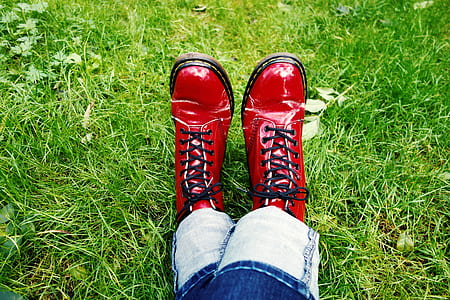 person wearing pair of leather boots sitting on grass