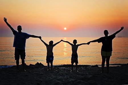 family silhouette on seashore during sunset