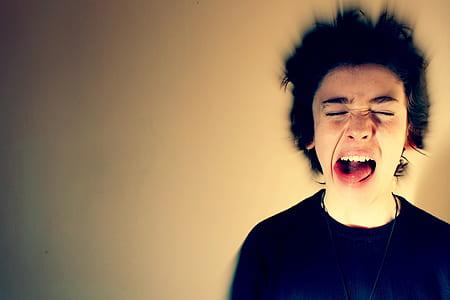 man wearing black crew-neck shirt opening his mouth