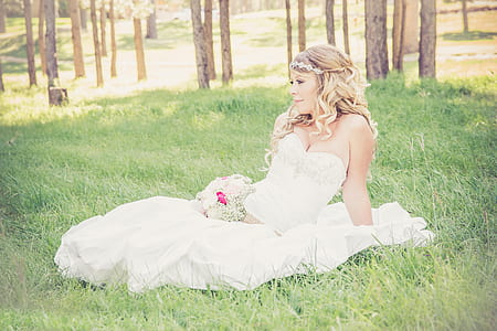 woman wearing white sweetheart neckline wedding dress sitting on green grass during daytime