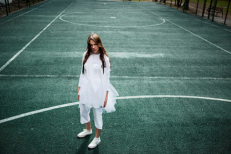 woman in white long-sleeved dress on game court
