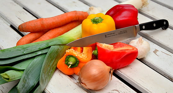 red and yellow bell peppers carrots and onion with black handle kitchen knife