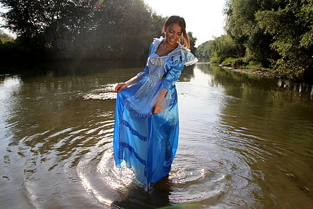 woman wearing blue dress standing on body of water during day time