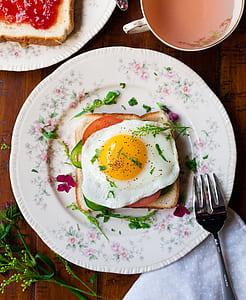 friend egg on bread on white ceramic plate beside stainless steel fork