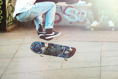man in white denim pants playing skateboard
