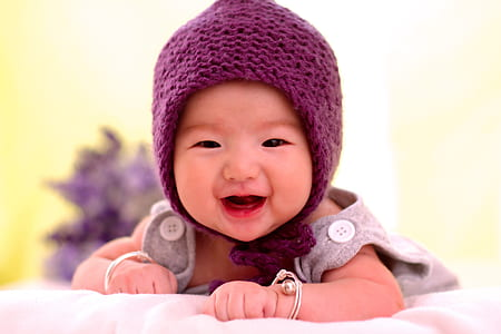 baby in grey clothes wearing purple knitted hat