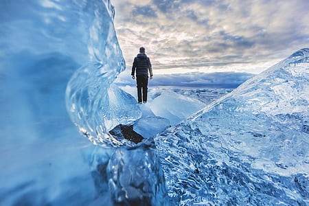 person wearing gray hoodie and black pants standing on ice