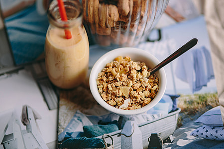 Jar full of walnuts with a fresh healthy shake and musli in a bowl