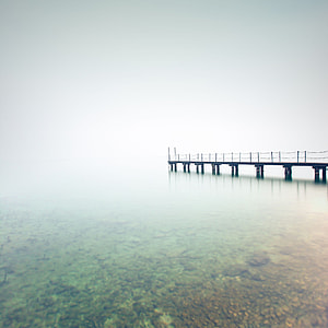 black wooden jetty on body of water