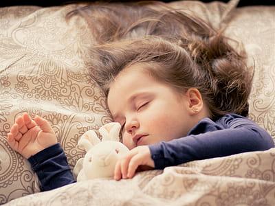 girl sleeping beside bunny plush toy during daytime