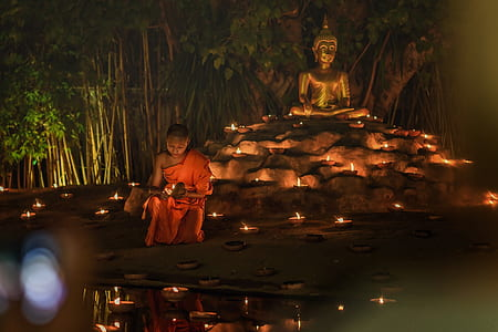 man wearing monk suit behind Gautama statue during nighttime