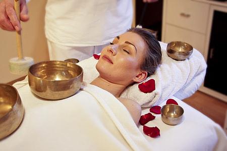 woman lying on white massage bed