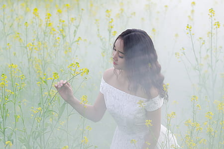 woman wearing white off-shoulder dress holding yellow flower